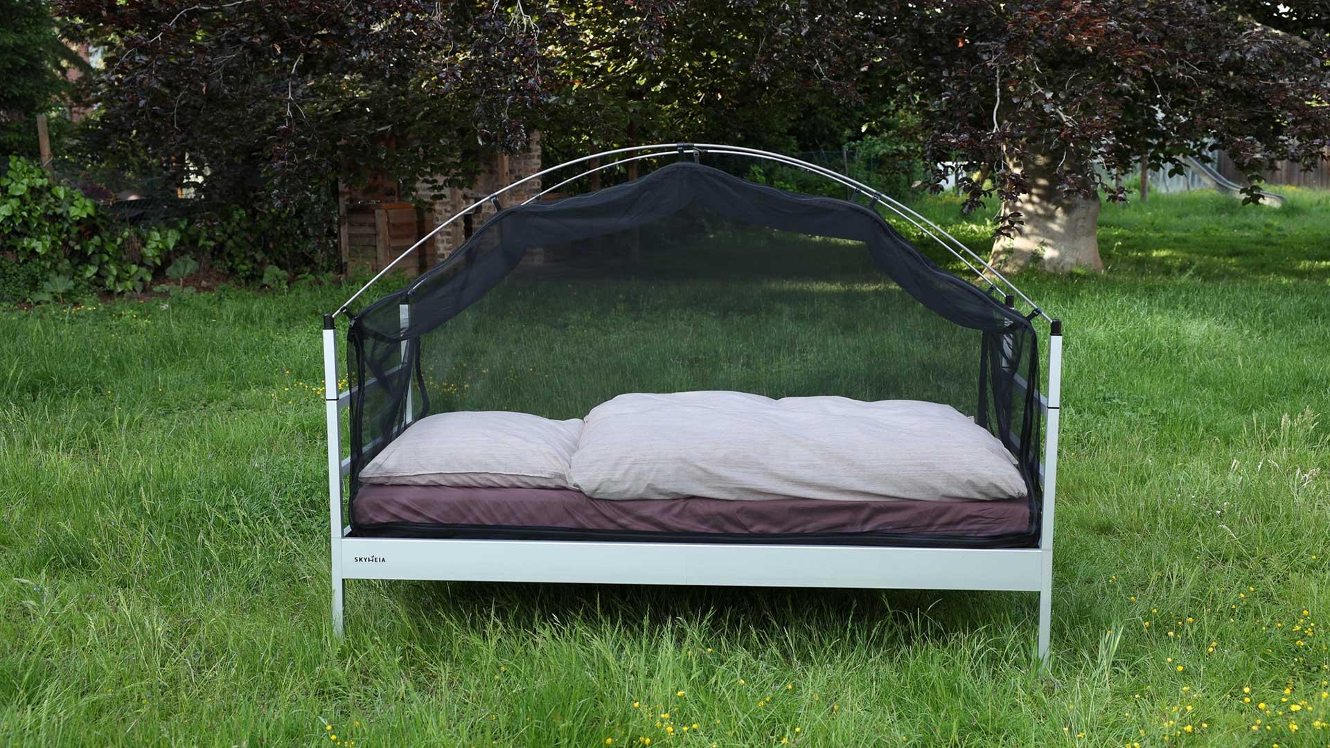 Man sieht das Outdoor-Bett SkyHeia auf einer Wiese stehend mit einem Moskitonetz, dass es kumpelartig umspannt.