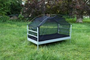 Die SkyHeia, das Outdoor-Bett zum Draußen Schlafen, steht auf einer Wiese. Es ist weder Matratze noch Bettwäsche aufgelegt. Das Bett ist jedoch umhüllt von einem schwarzen Moskitonetz.