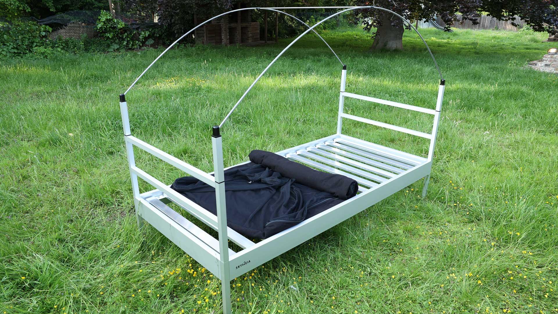 Die SkyHeia, das Outdoor-Bett steht auf einer Wiese, Matratze und Bettwäsche sind nicht mehr auf dem Outdoor-Bett. Man sieht den teils eingerollten Moskitoschutz, der einen Blick auf das Lattenrost aus Aluminium freigibt.