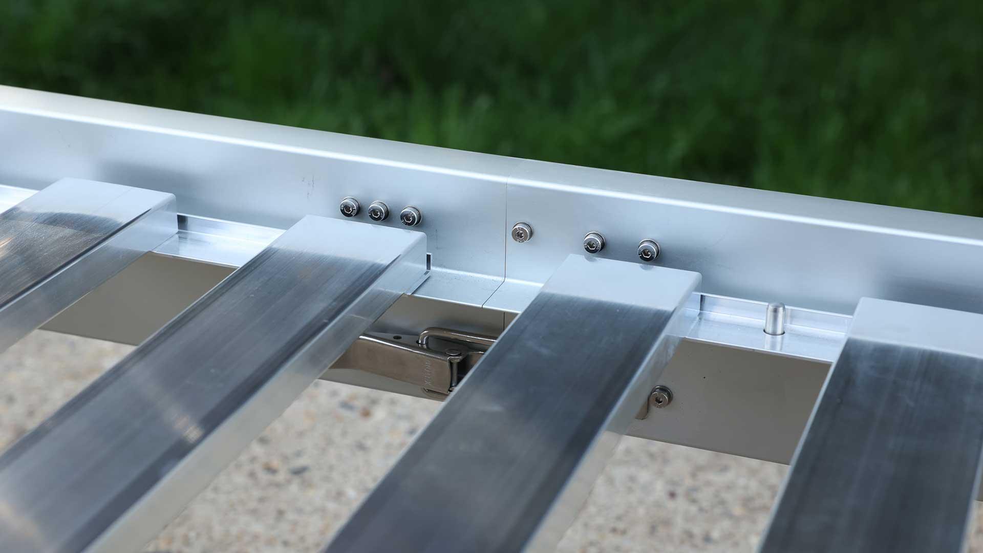 Die 4 Lattenrost-Elemente aus unbehandeltem Aluminium werden in den Bettrahmen eingelegt. Bei der Positionierung helfen Edelstahl-Bolzen, die im Rahmenprofil integriert sind.