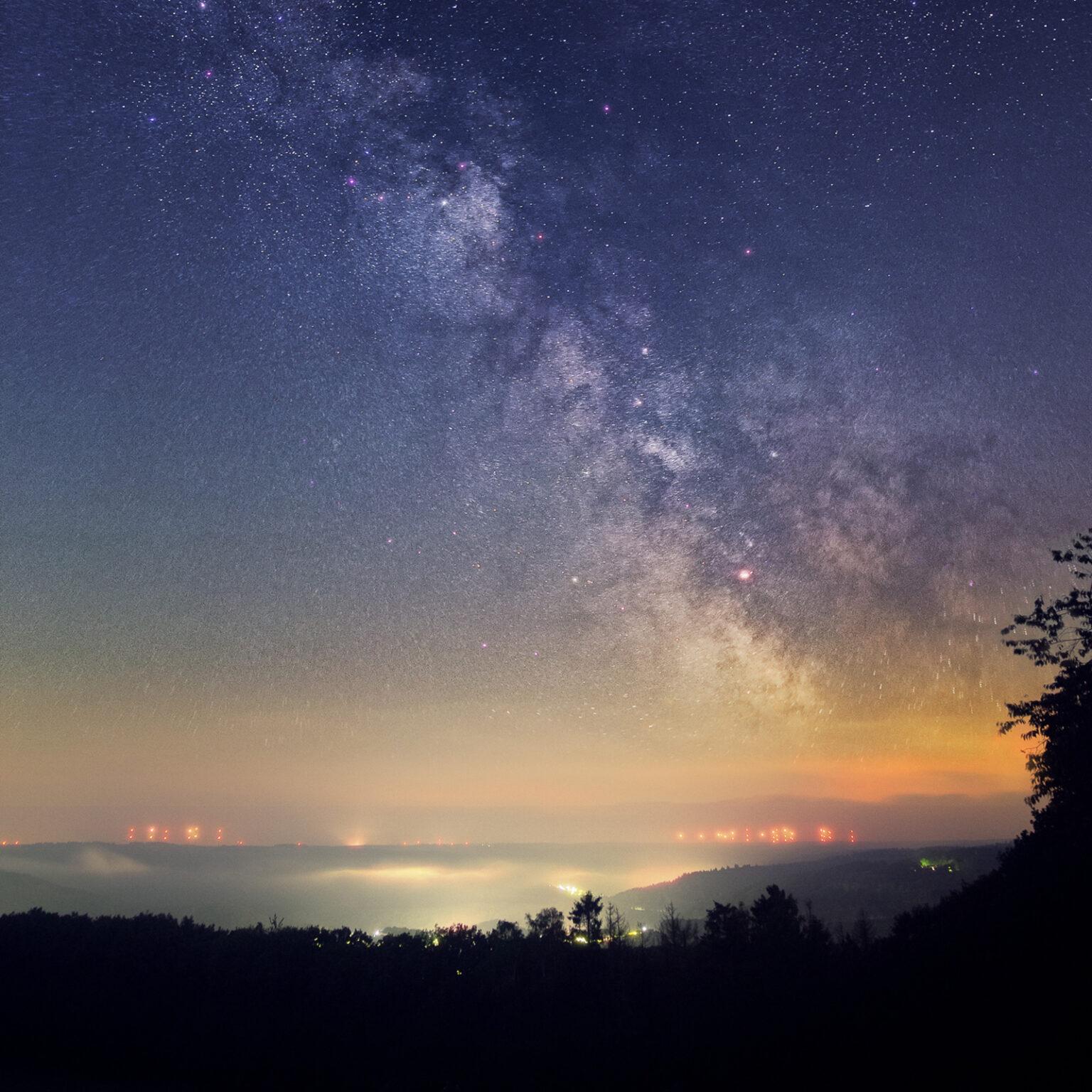 Das Bild zeigt einen üppigen Sternenhimmel über dem Rursee in der Eifel. Von einigen Ortschaft geht eine leichte Lichtverschmutzung aus. Die Sterne sind dennoch sehr gut zu sehen.