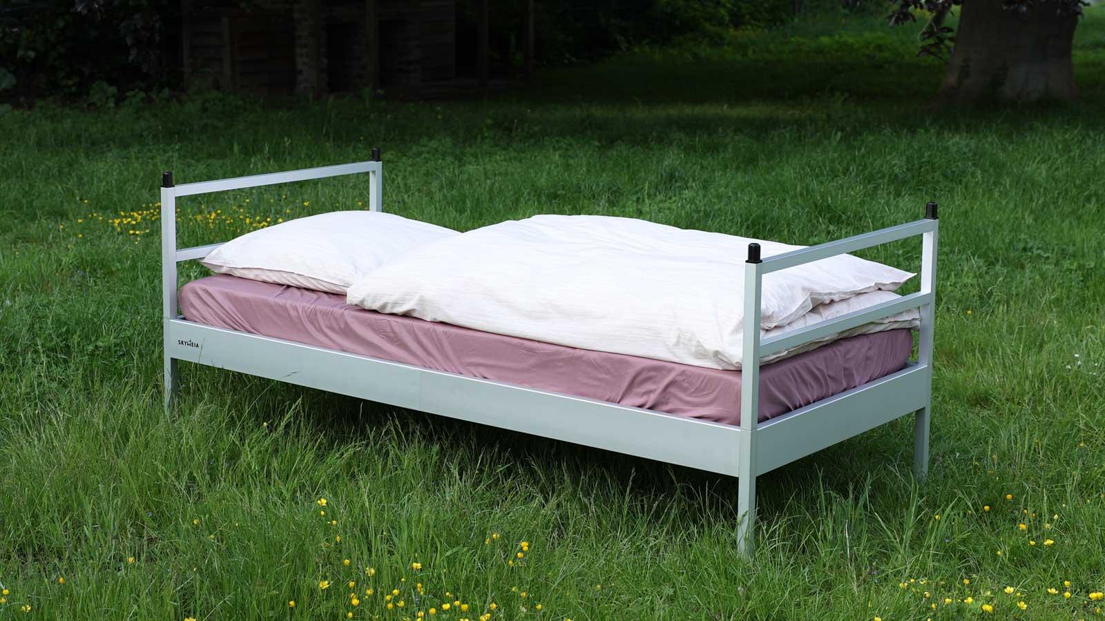 Die SkyHeia, das Outdoor-Bett, steht auf einer Wiese. Man sieht das Bett in seiner Grundausstattung mit weißer Bettwäsche und violettem Bettlaken.