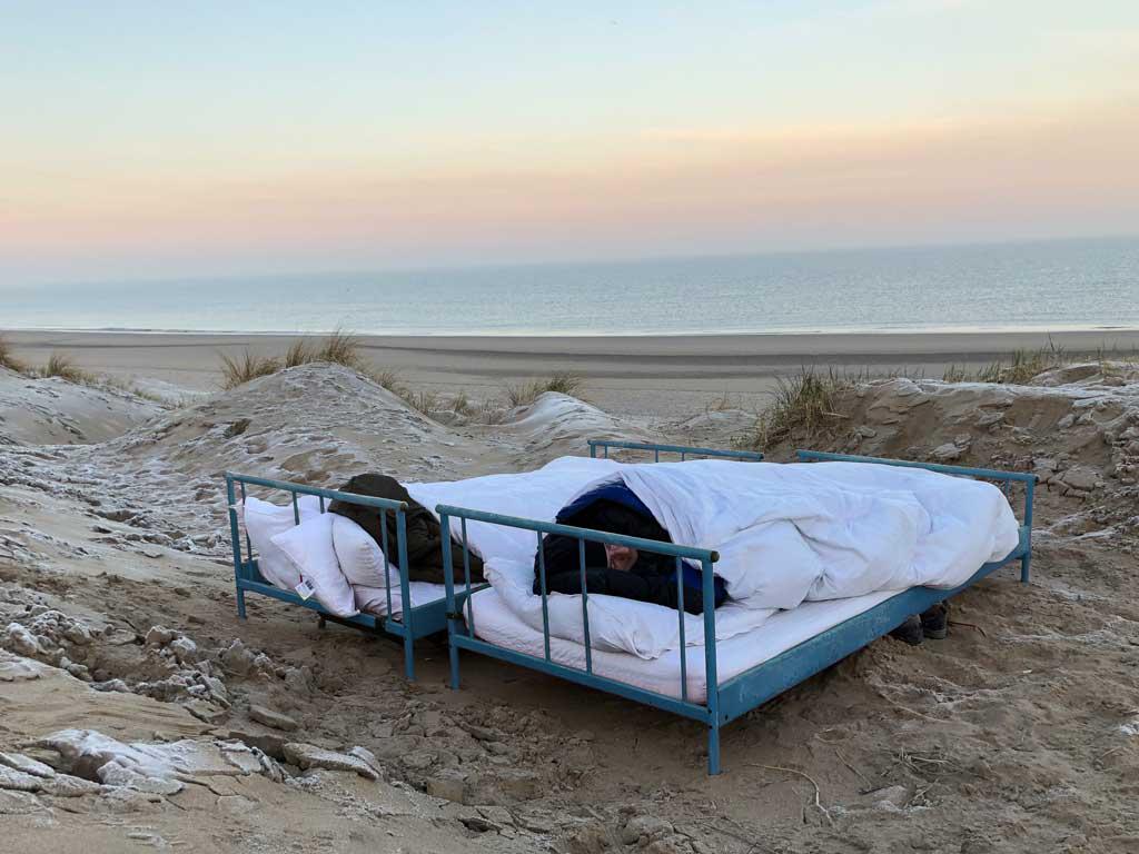 Schlafen am Strand: Zwei normale Betten (kein spezielles Outdoor-Bett) stehen am Strand an der Nordsee in Wassenaar bei Katwijk. Der Blick geht über die weiße Bettwäsche und das Fußende hinaus auf das Meer. Es ist kurz vor Sonnenaufgang.