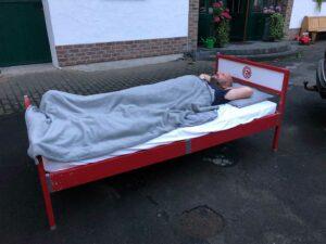 Ein Mann liegt in der SkyHeia, damals noch in der Farbe rot. Er ist zugedeckt mit einer grauen Bettdecke.